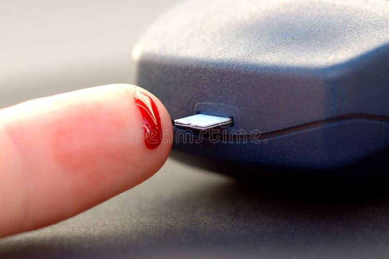 Bloedonderzoekstrook met geprikte vinger stock foto's