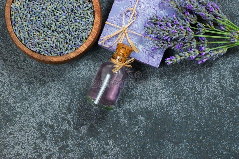 Bloeien de lavendel natuurlijke zeep en de lavendelolie met verse lavendel en droge lavendelzaden op grijze rustieke lijst stock fotografie