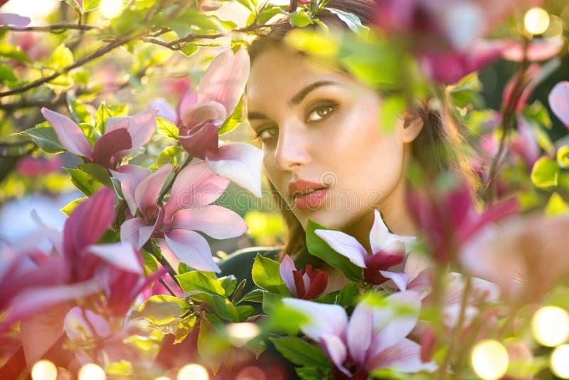 Bloeiende magnoliabomen De ontroerende en ruikende van de de lentemagnolia bloemen van de schoonheids jonge vrouw stock fotografie