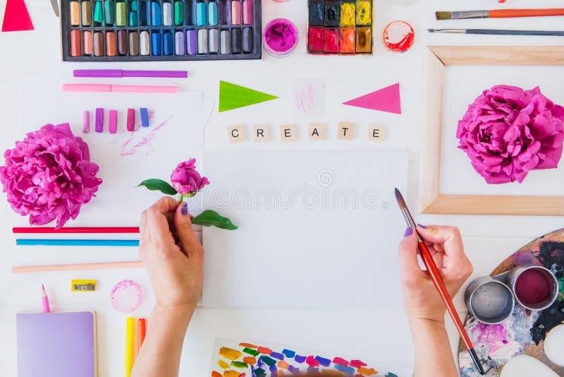 Bloeit de Topview Vrouwelijke Handen die borstel over leeg canvas met Create houden die en het schilderen materialen, pioen op wi royalty-vrije stock afbeeldingen