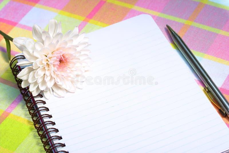 Bloem met notitieboekje en pen royalty-vrije stock afbeelding