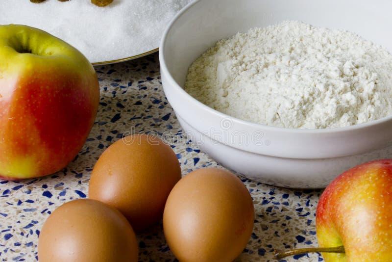 Bloem, suiker, rozijnen, eieren en appelen voor eigengemaakte gebakjes stock foto's