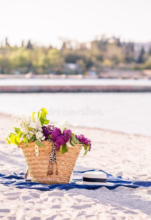 Bloem van sering De hoed van de vrouwenzomer met een lint en een boeket van lilac bloemen op een blauwe achtergrond Hoogste menin royalty-vrije stock foto