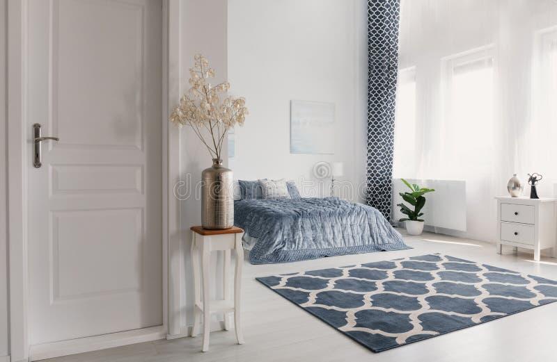 Bloem in zilveren vaas op de houten lijst naast gesloten deur aan elegante de stijlslaapkamer van New York met gevormd tapijt en  royalty-vrije stock afbeeldingen