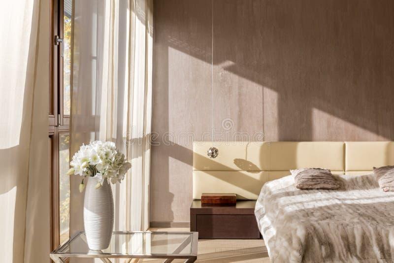 Bloemen in beige slaapkamer royalty-vrije stock afbeeldingen