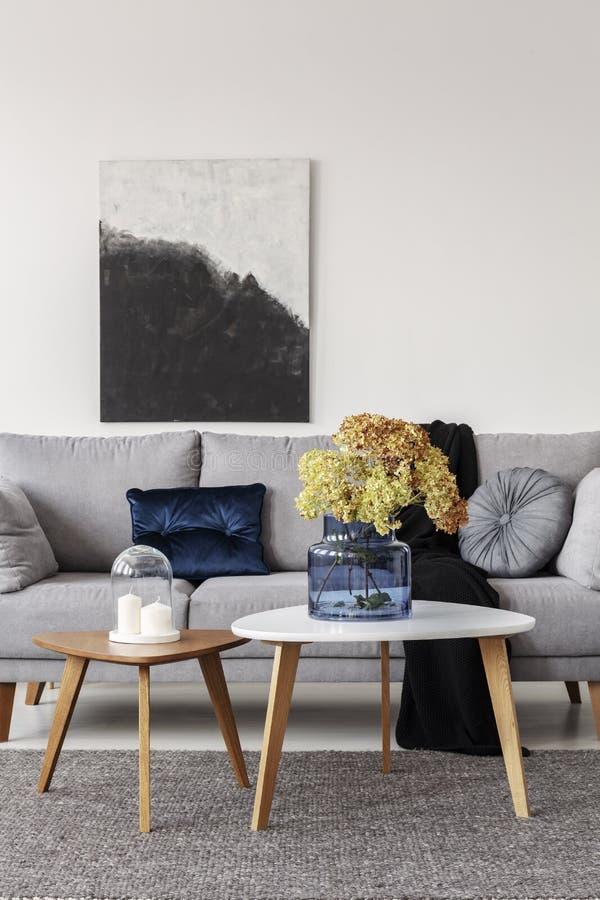 Bloemen in blauwe glasvaas en twee witte kaarsen op houten koffietafels in grijze elegante woonkamer met comfortabele bank stock fotografie