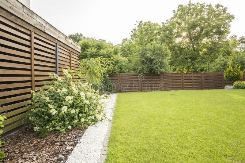 Bloemen, bomen en groen gras in de tuin van huis met het houten scherm Echte foto stock foto's
