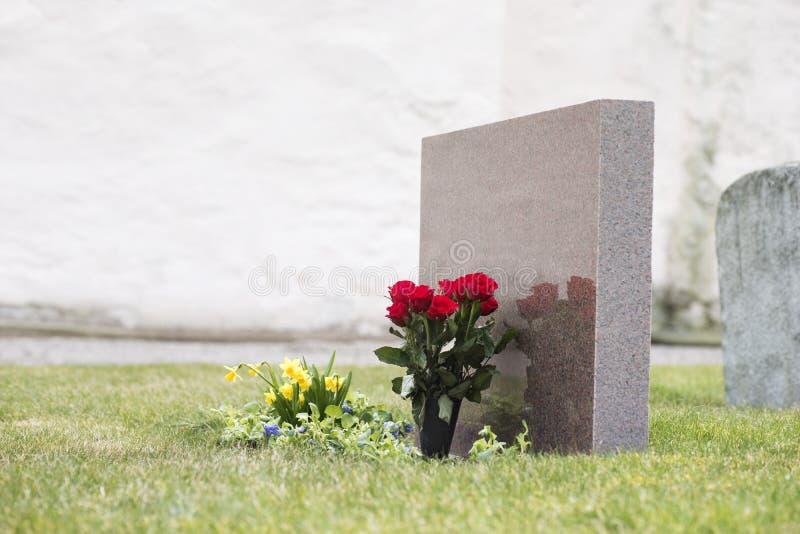 Bloemen door grafsteen stock foto's