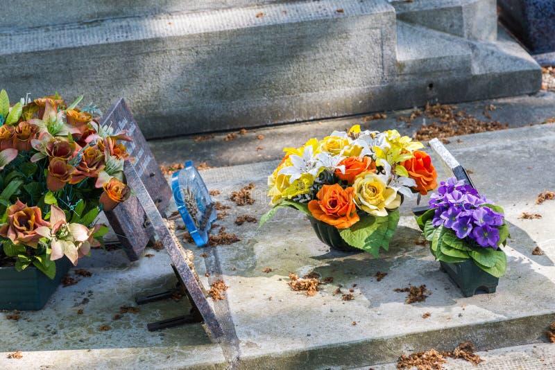 Bloemen in een begraafplaats met grafstenen op achtergrond royalty-vrije stock fotografie