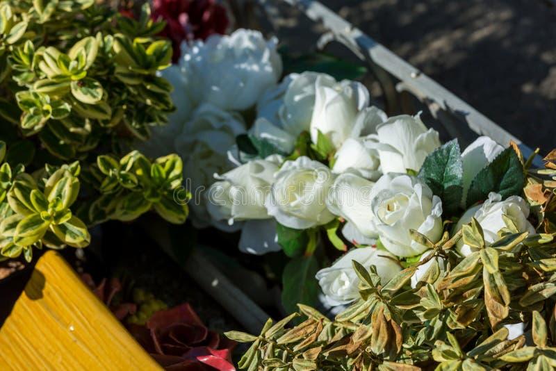 Bloemen in een begraafplaats met grafstenen op achtergrond stock foto