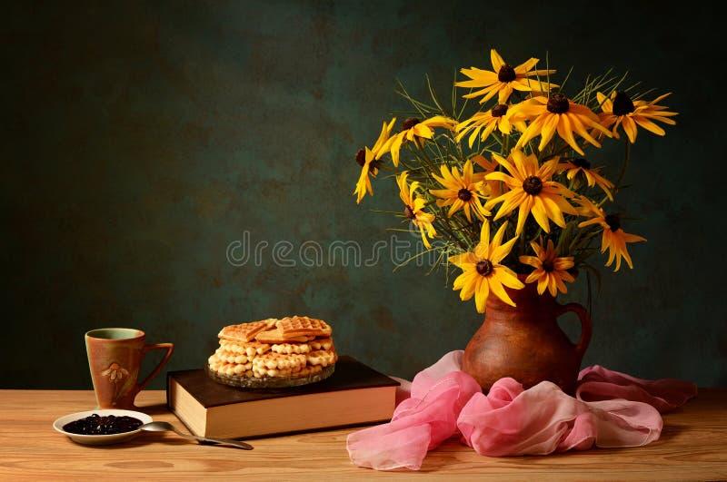 Bloemen in een vaas, boeken en cakes royalty-vrije stock foto
