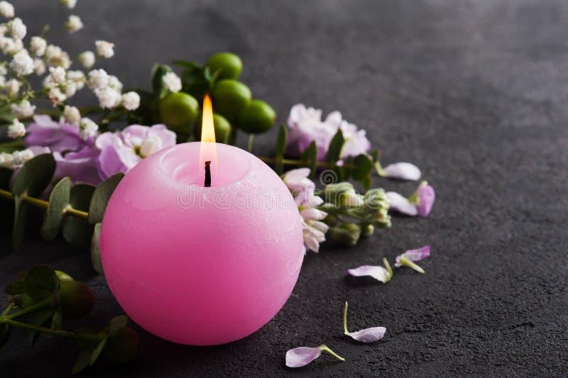 Bloemen en aangestoken kaars stock afbeelding