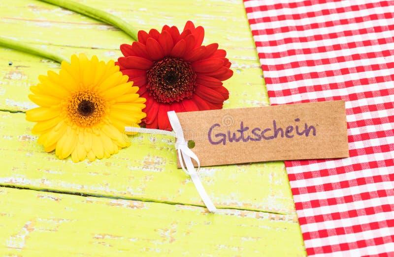 Bloemen en giftkaart met Duitse woord, Gutschein, middelenbon of coupon stock afbeeldingen