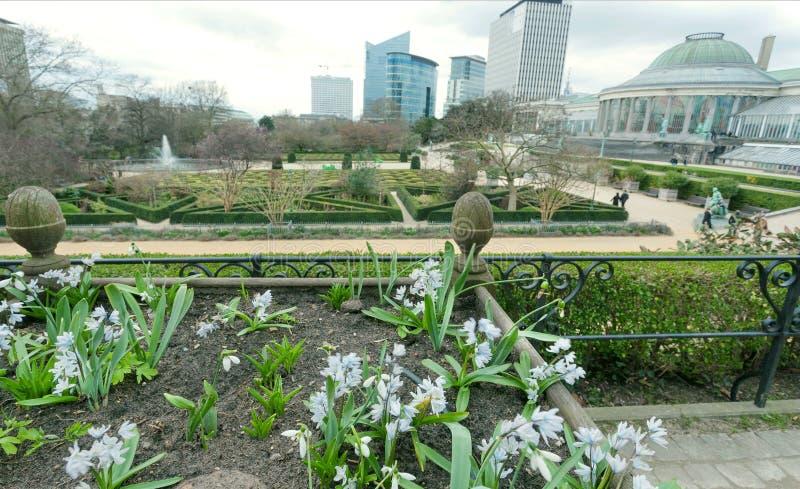 Bloemen en groen gebied rond de bouw van Le Botanique met oranjerie, stedelijke torens, tuin en het lopen van mensen van Brussel royalty-vrije stock foto's