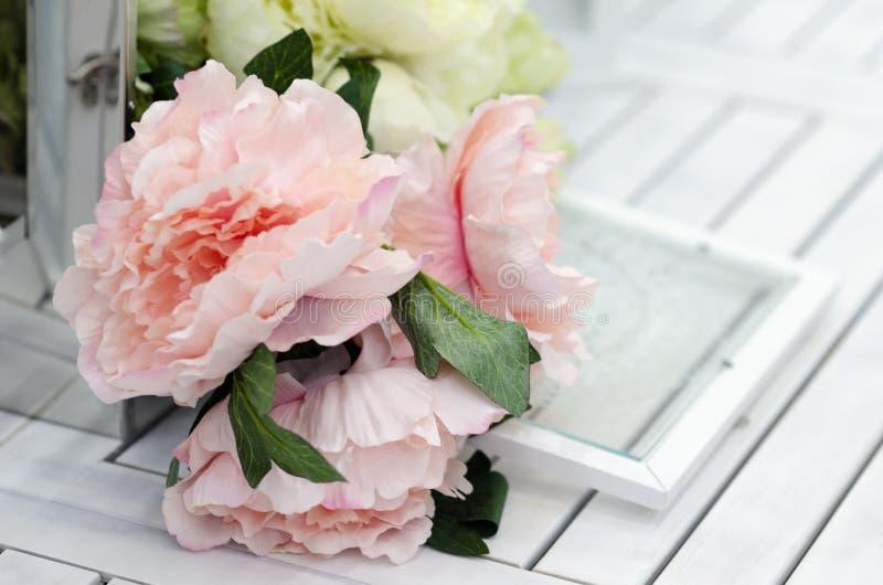 Bloemen en lampen op de witte houten lijst stock afbeeldingen