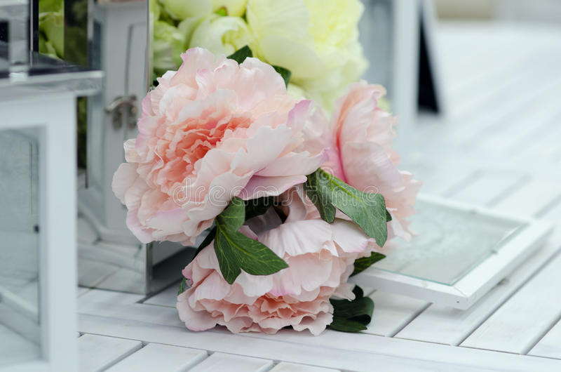 Bloemen en lampen op de witte houten lijst stock fotografie