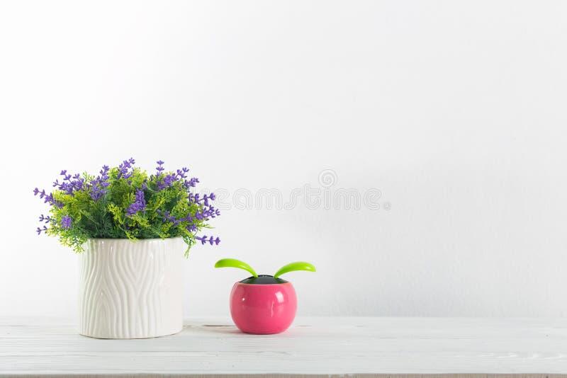 Bloemen en pot op een wit met muurplank stock fotografie