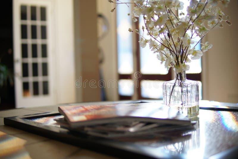 Bloemen en tijdschriften in huis stock foto's