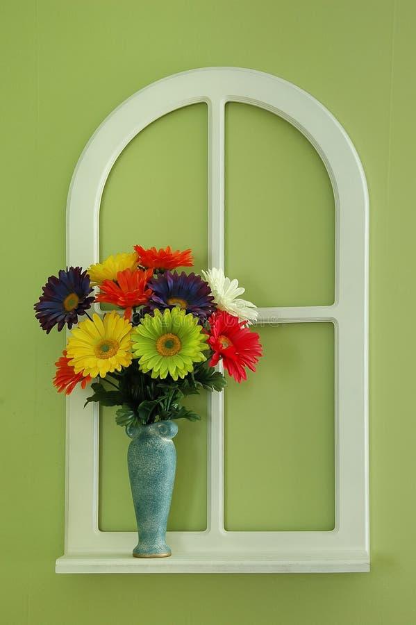 Bloemen en vaas door een venster stock fotografie