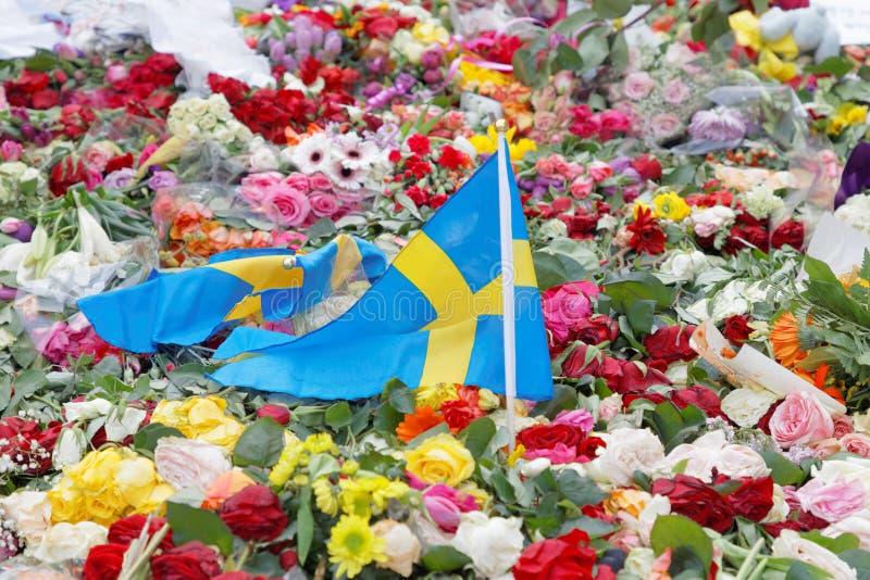Bloemen en Zweedse vlag van mensen die eerbied betalen aan victi royalty-vrije stock foto