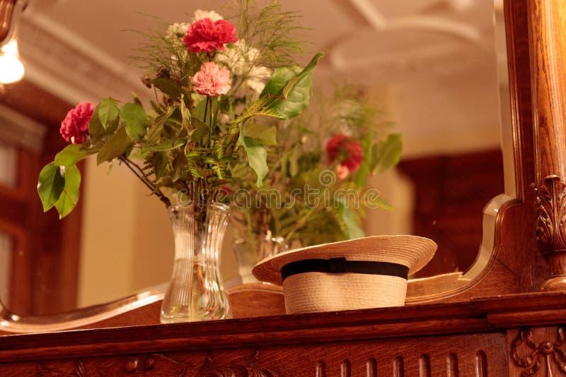 Bloemen & Hoed in Spiegel van Elegant Huis stock foto's