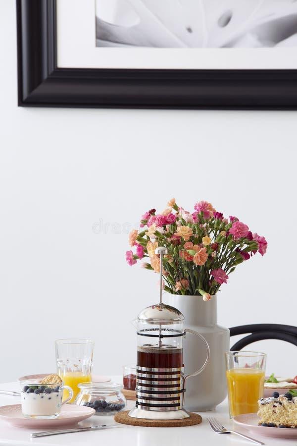 Bloemen, jus d'orange en thee op lijst in wit restaurantbinnenland met affiche Echte foto royalty-vrije stock afbeeldingen