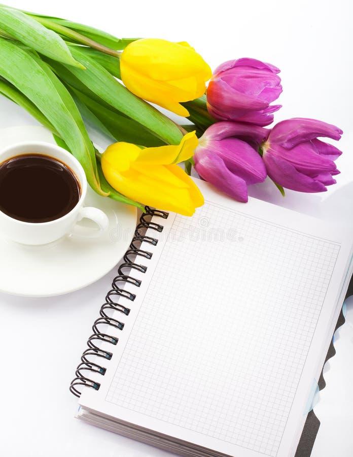 Bloemen, koffie en notitieboekje. royalty-vrije stock afbeelding