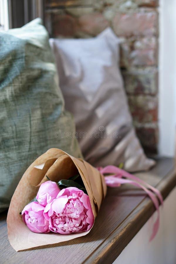 Bloemen in kraftpapier-document op textielachtergrond en houten vensterbank worden verpakt die stock foto's