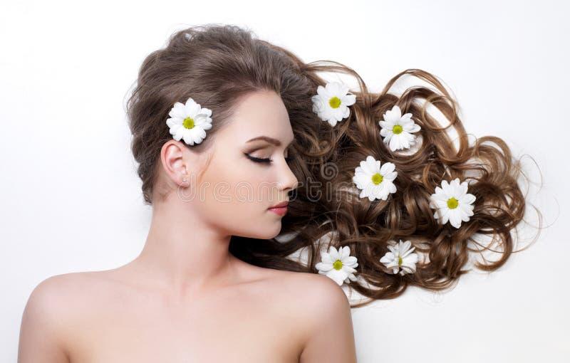 Bloemen in lang haar van tienermeisje royalty-vrije stock foto