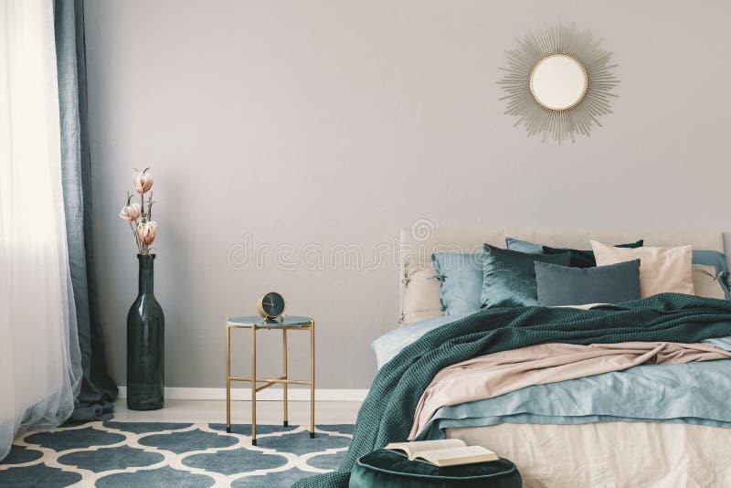 Bloemen in modieuze fles zoals vaas naast in nightstand met klok in mooi slaapkamerbinnenland met beige en smaragdgroen royalty-vrije stock afbeeldingen