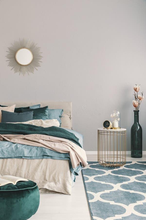 Bloemen in modieuze fles zoals vaas naast in nightstand met klok in mooi slaapkamerbinnenland met beige en smaragdgroen royalty-vrije stock afbeelding