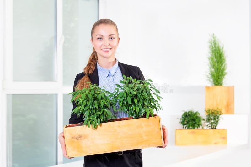 Bloemen Naadloos Patroon Aantrekkelijke jonge onderneemster die zich in modern zolderbureau bevinden die een doos met installatie royalty-vrije stock afbeeldingen