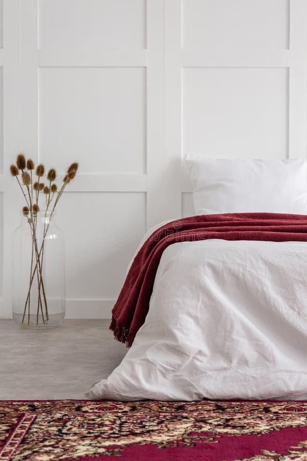 Bloemen naast bed met rode deken in wit slaapkamerbinnenland met gevormd tapijt stock afbeelding