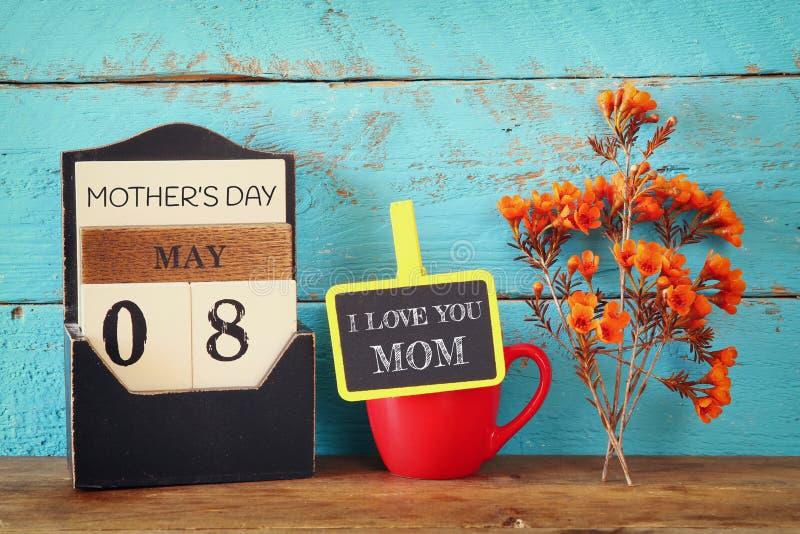 Bloemen naast bord met uitdrukking op houten lijst Het gelukkige concept van de Moederdag stock foto's