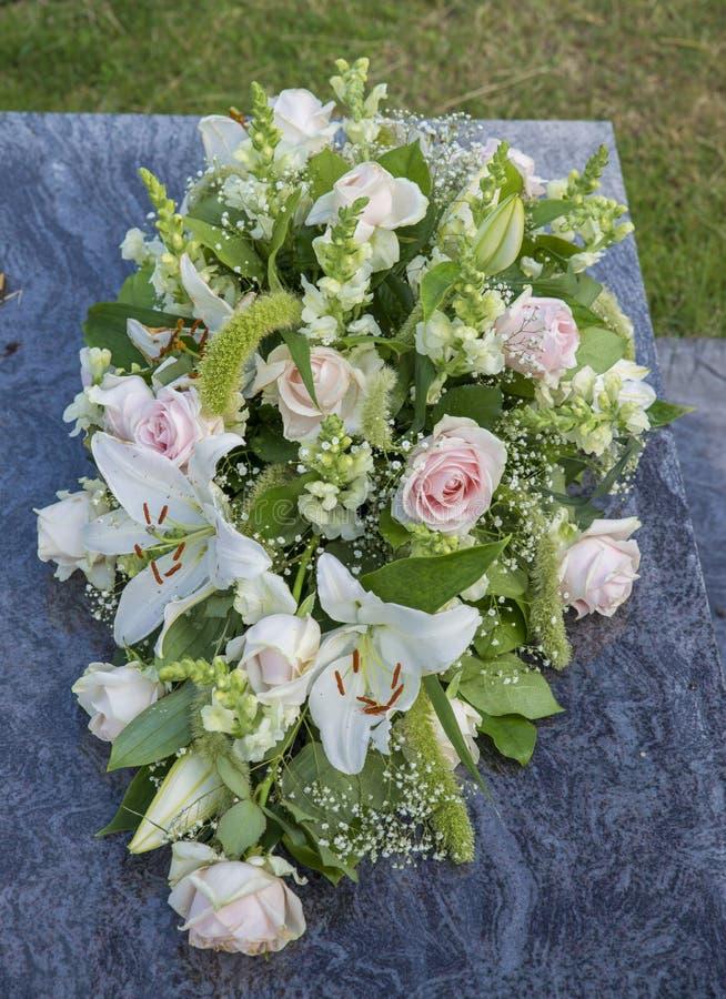 Bloemen op een graf stock fotografie