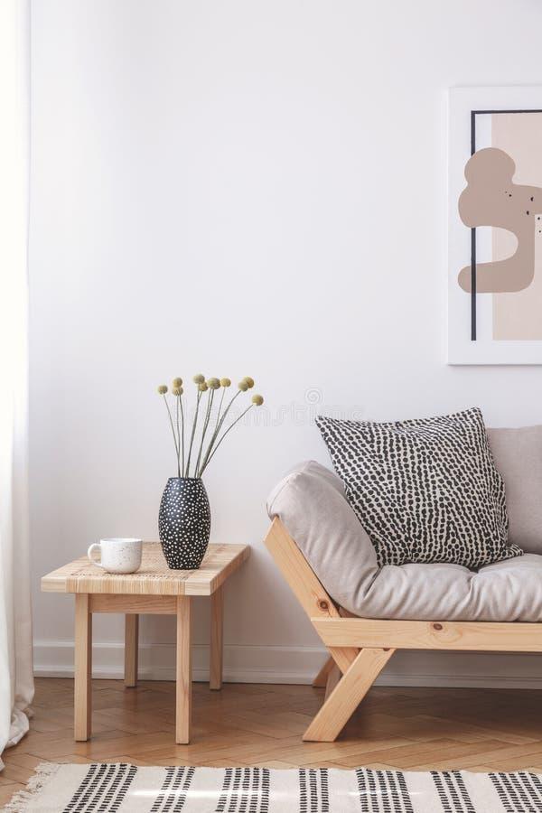 Bloemen op houten lijst naast beige laag met kussen in vlak binnenlands met affiche Echte foto royalty-vrije stock afbeelding