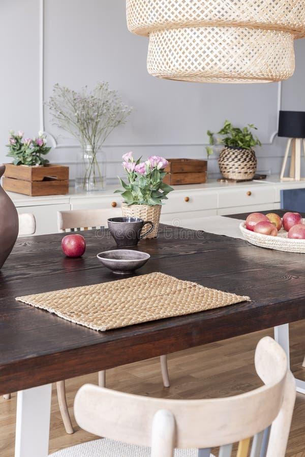 Bloemen op houten lijst onder lamp in modern helder eetkamerbinnenland met stoel Echte foto stock afbeeldingen