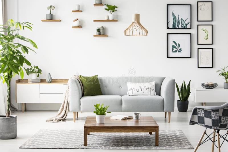 Bloemen op houten lijst voor grijze bank in scandi vlak binnenlands met affiches en leunstoel Echte foto stock afbeeldingen
