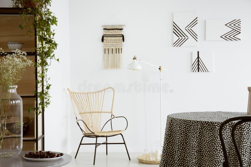Bloemen op lijst dichtbij moderne leunstoel in helder flatbinnenland met lamp en affiches Echte foto royalty-vrije stock fotografie