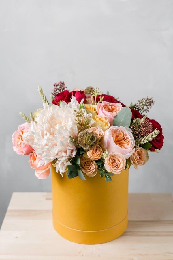 Bloemen in ronde luxe huidige doos Boeket van gemengde bloemen in yelowdocument vakje stock foto