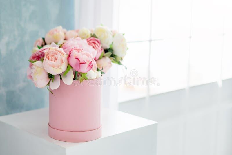 Bloemen in ronde luxe huidige doos Boeket van roze en witte pioenen in document vakje dichtbij het venster Model van hoedendoos royalty-vrije stock foto