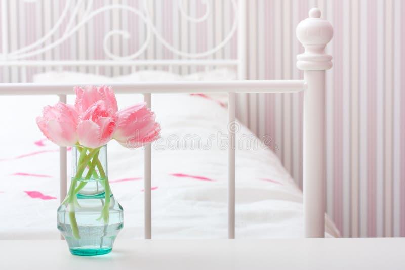 Bloemen in vaas in een slaapkamer. royalty-vrije stock afbeelding