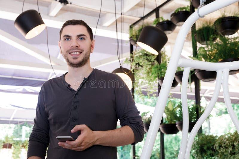 Bloemen van de de koffieserre van de mensenjongen ontwerpen de jonge het binnenlandse gelukkige portret van vele potten verschill stock foto