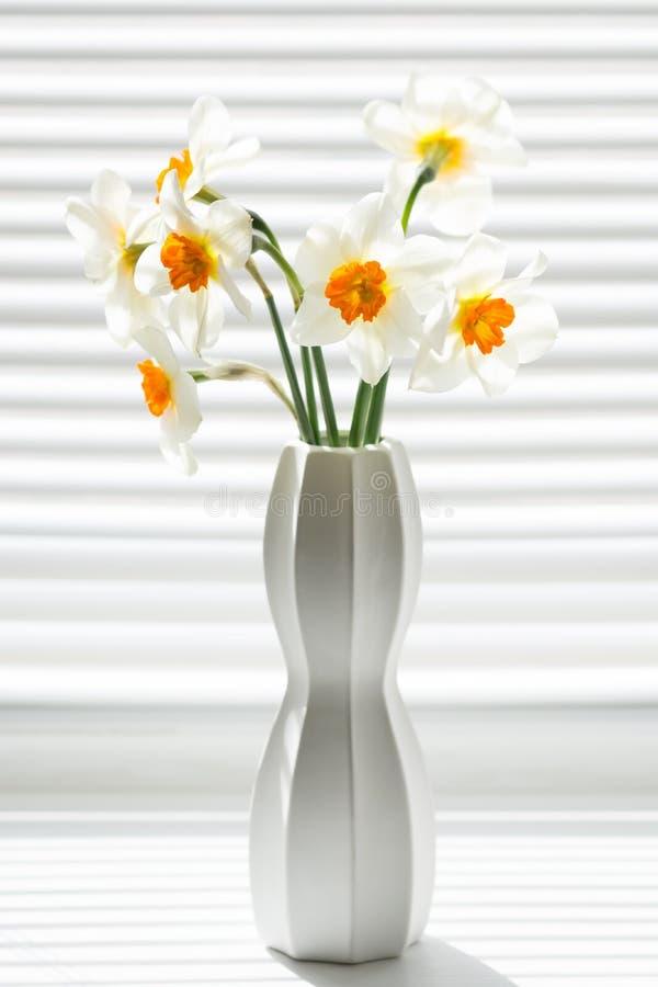 Bloemen van gele narcissen in een witte vaas op een venster met jaloezie royalty-vrije stock foto