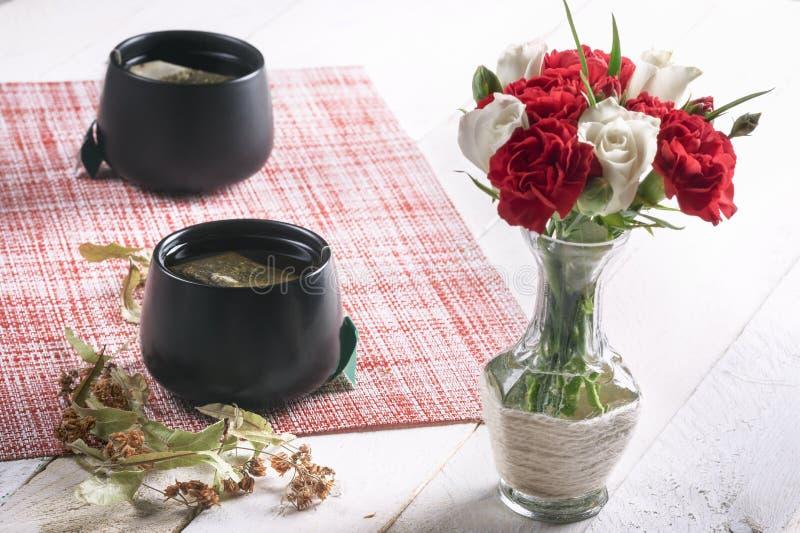 Bloemenboeket in een vaas en lindethee stock fotografie