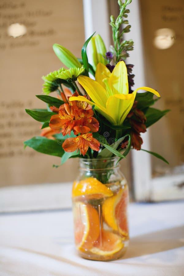 Bloemenboeket in kruiken met sinaasappelen stock afbeeldingen