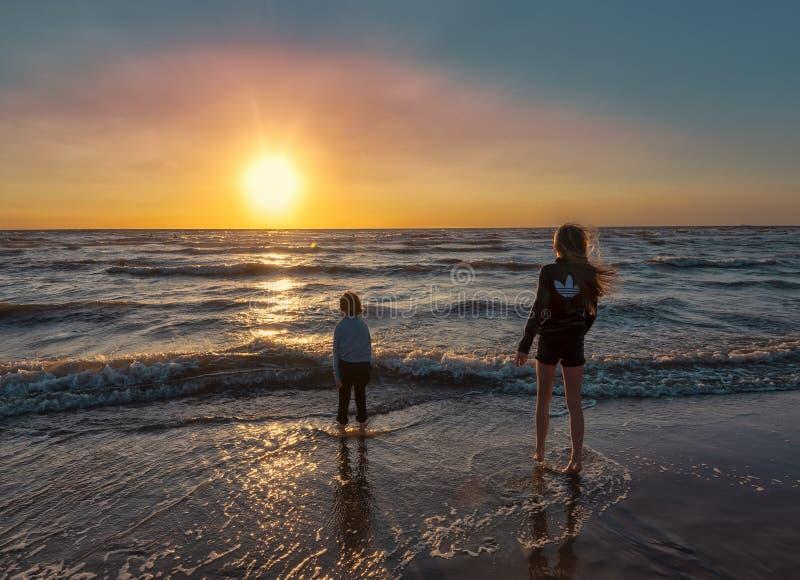 Bloemendaal,荷兰,8-8-2018 使用在与他们的脚的海滩的男孩和女孩在涨潮的波浪,当t时 免版税库存照片