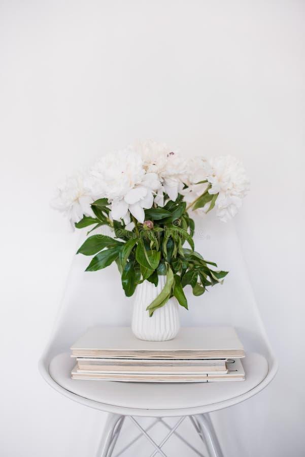 Bloemendecor, verse pioenen op ontwerperstoel in witte ruimte int. stock afbeelding