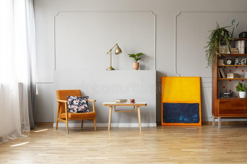 Bloemendruk op een oranje beklede leunstoel in een elegant woonkamerbinnenland met hardhoutvloer en plaats voor een bank Echt p stock afbeelding