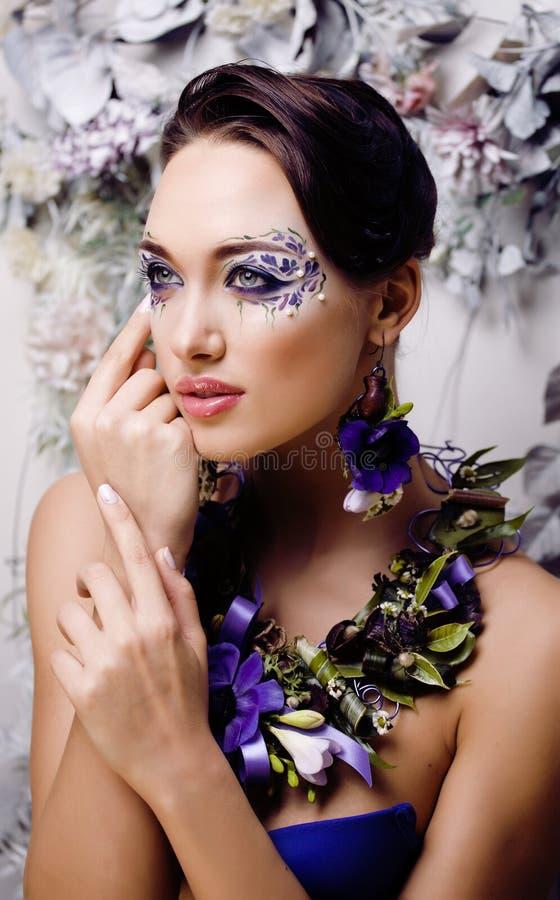 Bloemengezichtskunst met anemoon in juwelen, sensuele jonge donkerbruine vrouw in studio dichte omhooggaand stock afbeelding